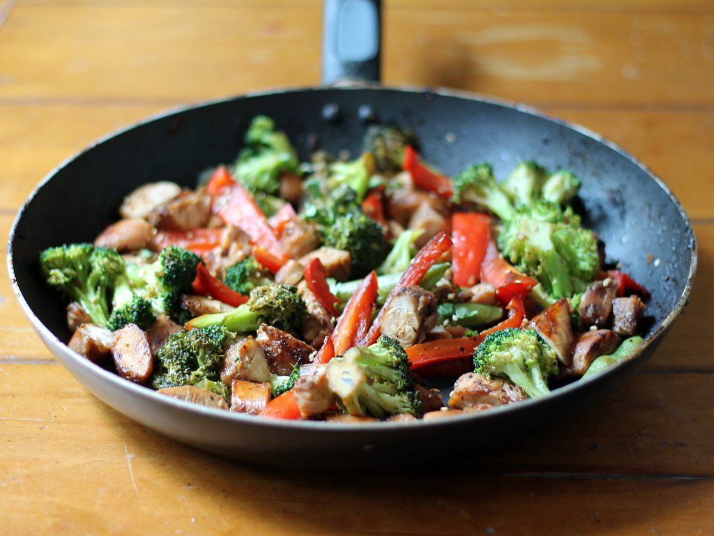 Sesame chicken stir fry in a pan on a table