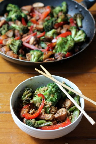 sesame ginger chicken stir fry in a bowl and next to a pan