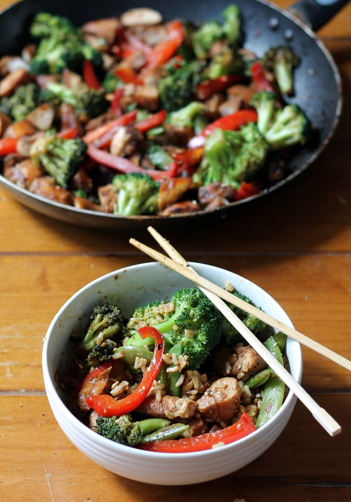 Broccoli, chicken and red peppers in a stir fry pan and in a white bowl with chopsticks