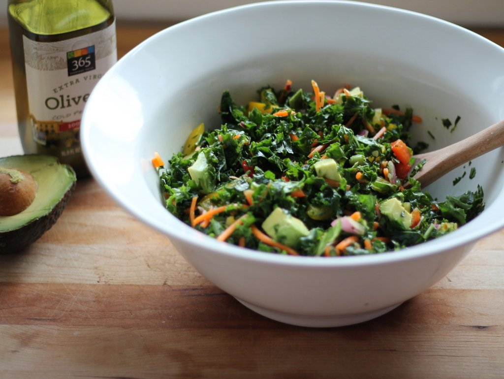 Kale rainbow detox salad in a white bowl next to avocado and olive oil