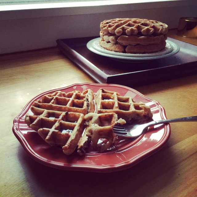 Waffle on a plate with a stack of waffles in the background