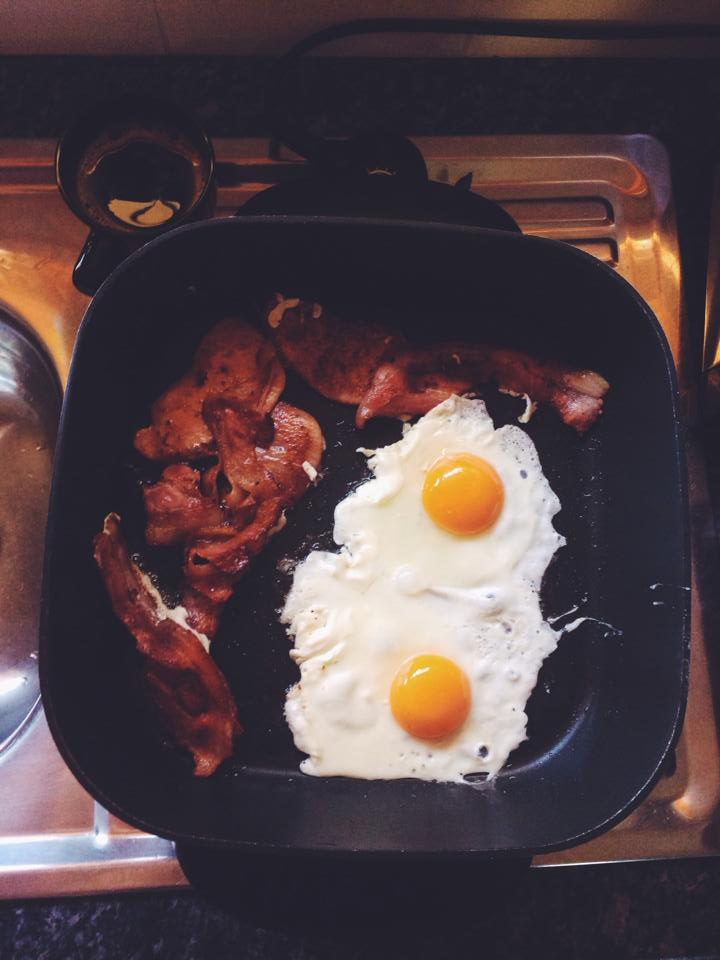 Eggs and bacon cooking on a skillet