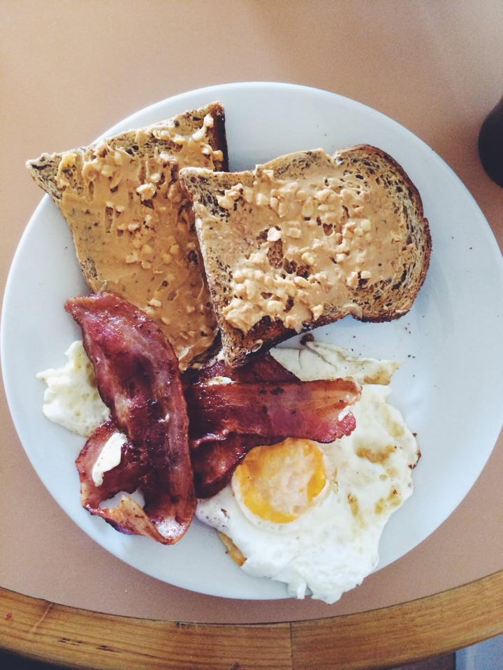 Bacon, eggs, and toast with peanut butter on a plate