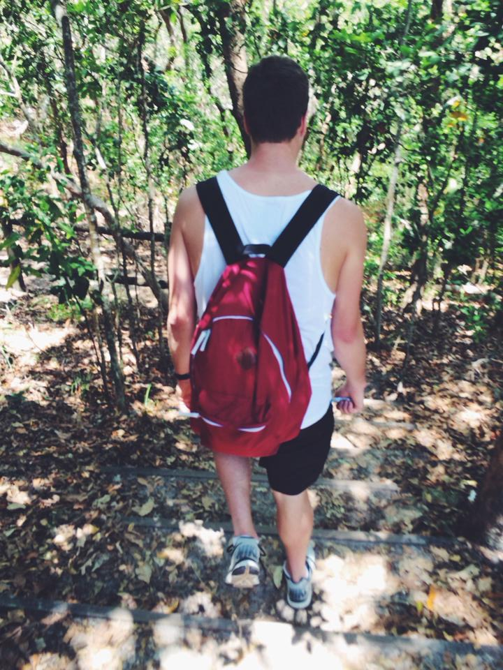Tony walking in the forest with a red backpack