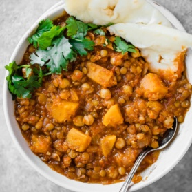 lentil moroccan stew in a bowl with naan and a spoon