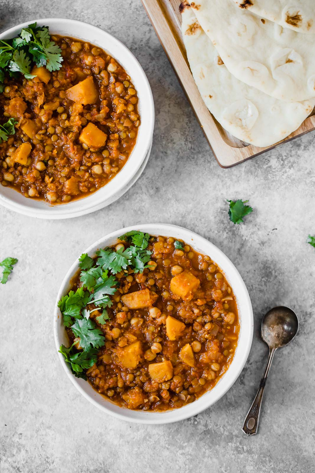 moroccan stew in two bowls topped with cilantro next to a sheet of naan bread