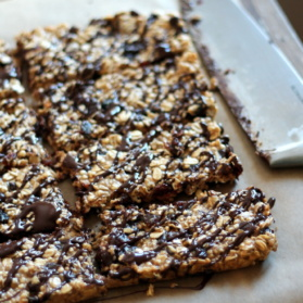 Dark chocolate cherry protein granola bars on parchment paper