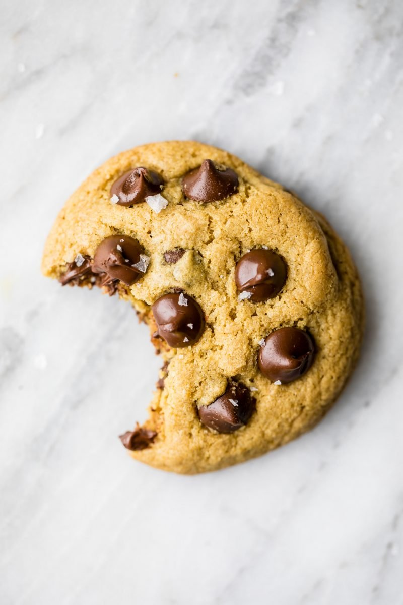 gluten free chocolate chip cookie on a marble board with a bite taken out of it