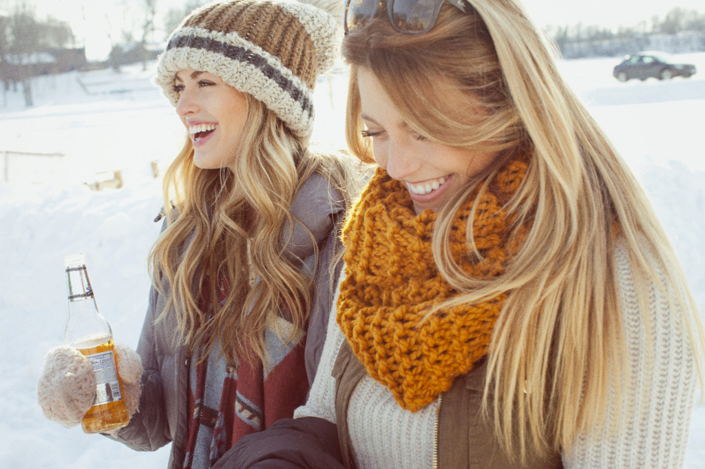 Two girls wearing scarves outside in the snow
