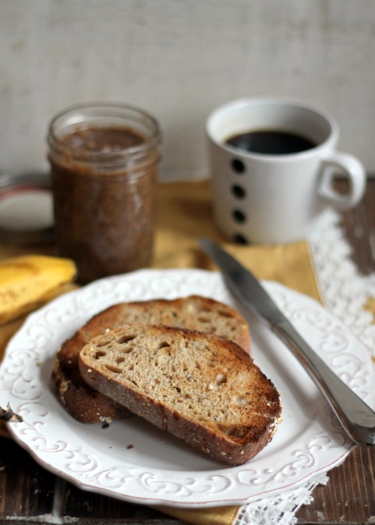 Toast on a plate next to a jar of homemade pecan butter