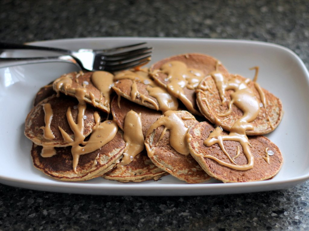 Applesauce oatmeal pancakes on a plate drizzled with peanut butter maple syrup