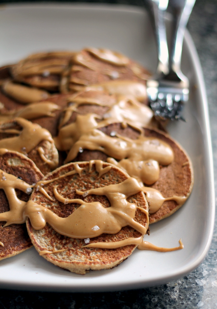 Applesauce oatmeal pancakes on a plate with peanut butter maple syrup