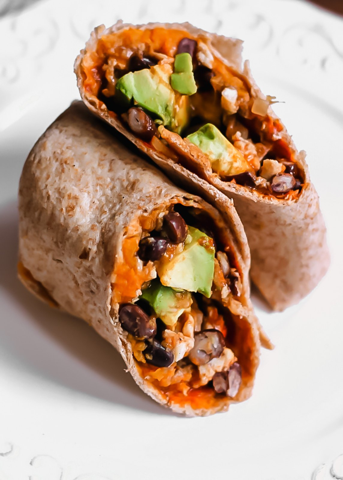 healthy breakfast burritos stuffed with sweet potatoes, black beans and avocado on a plate