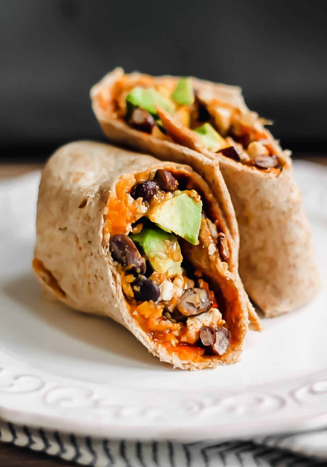 healthy breakfast burritos on a plate stuffed sweet potato avocado and black beans
