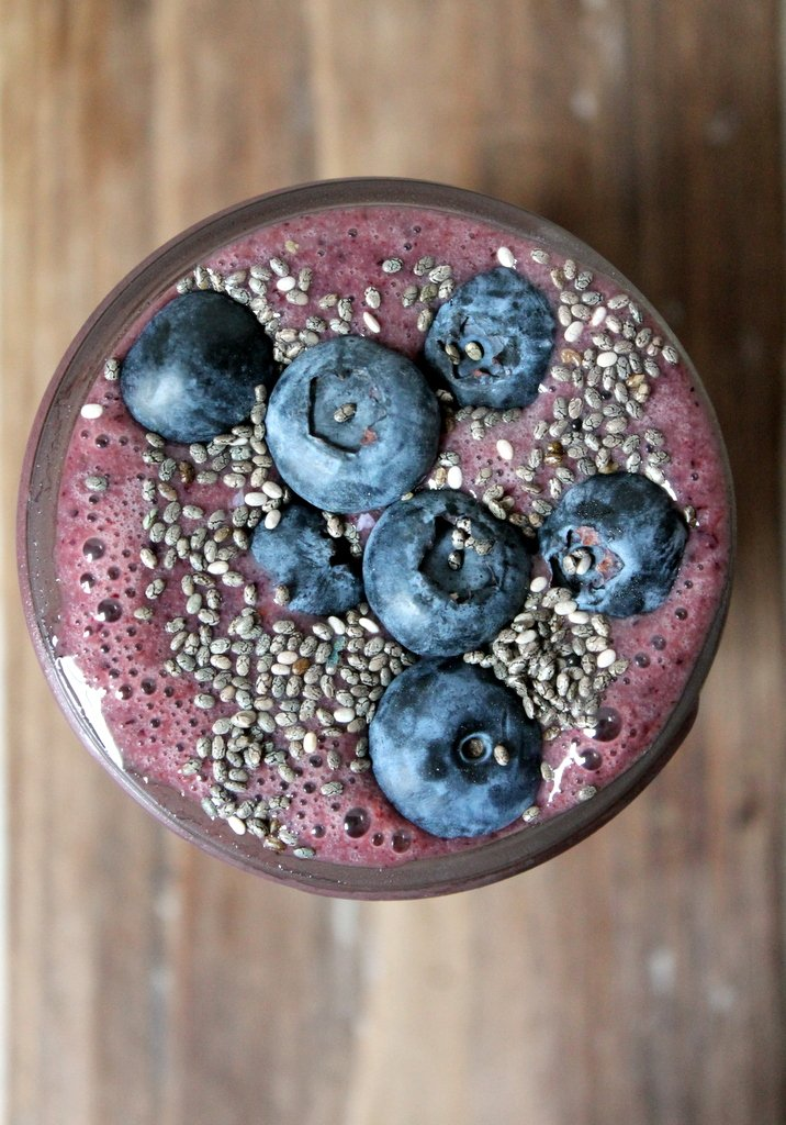 Power smoothie in a cup topped with blueberries and chia seeds
