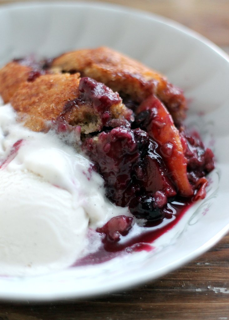 Peach blueberry cobbler in a bowl with ice cream