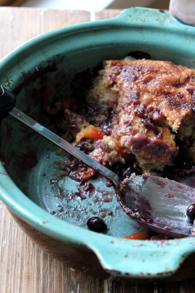 peach blueberry cobbler in a teal dish