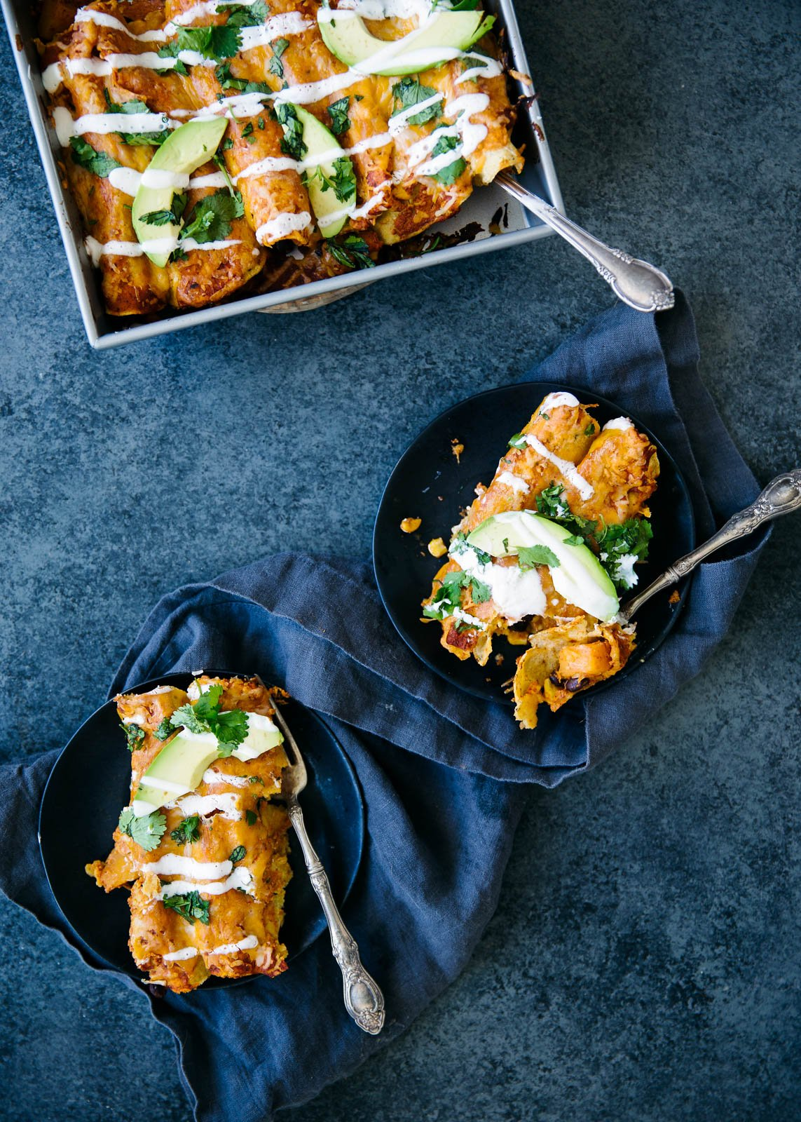 butternut squash black bean enchiladas in a pan and on two plates