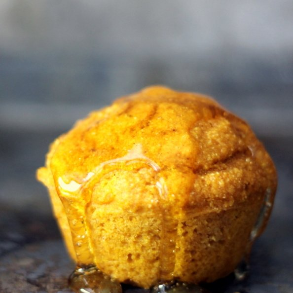 healthy pumpkin cornbread muffin drizzled with honey