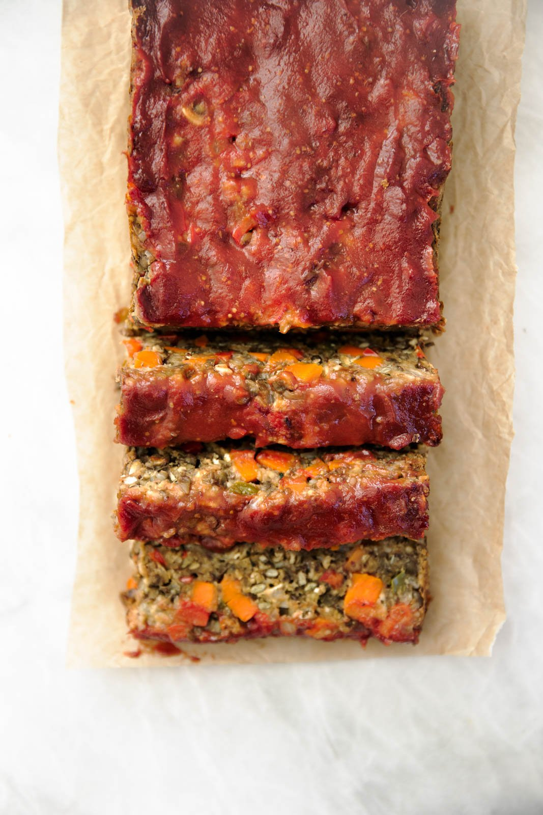 A lentil meat loaf on parchment paper on top of a white marble board