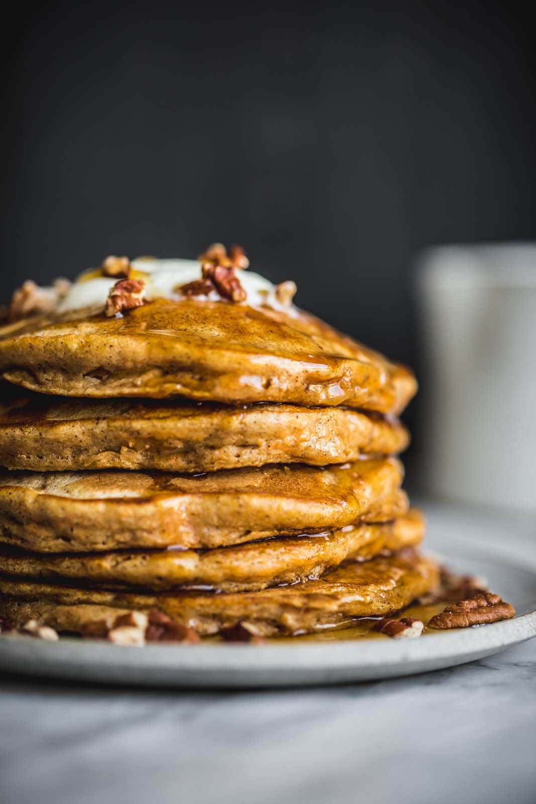 chai-spiced sweet potato pancakes on a plate topped with pecans