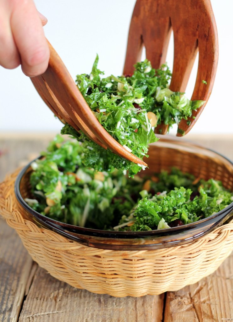 Kale salad in a wicker bowl with two wooden tongs