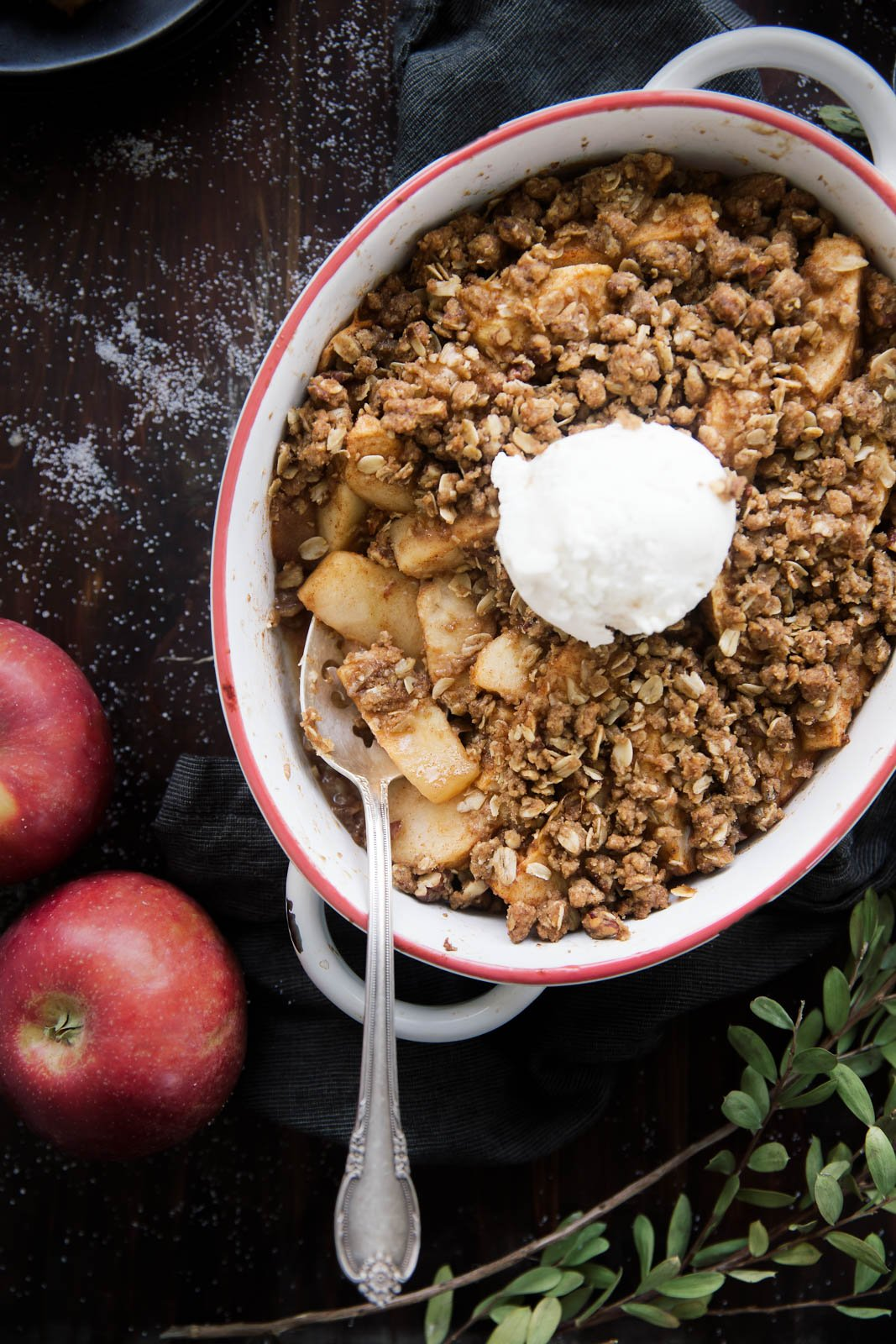 Maple pecan apple crisp in a baking dish with a spoon
