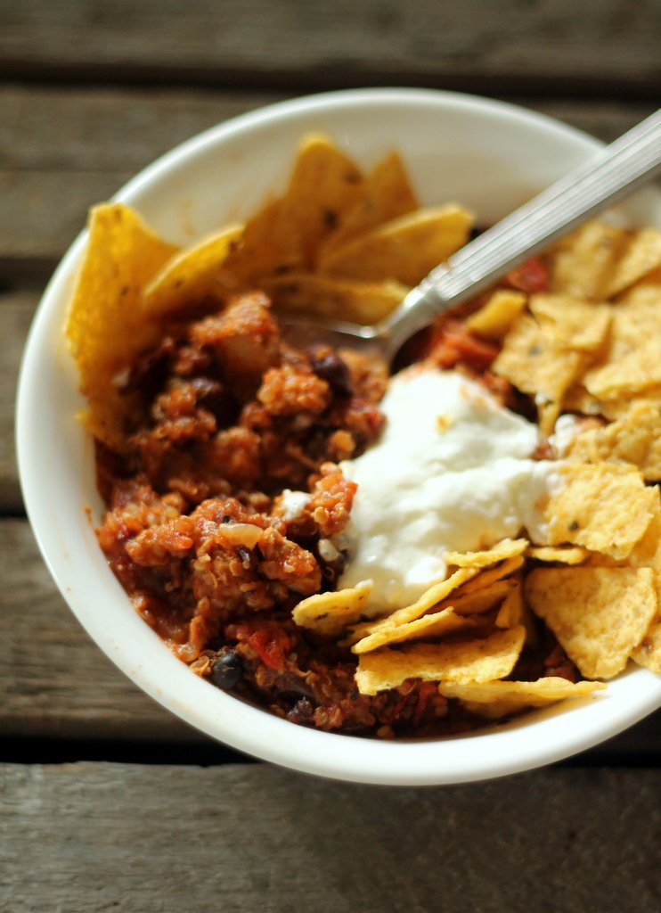 Healthy turkey quinoa chili in a bowl with tortilla chips and sour cream