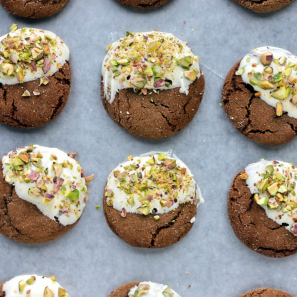 Soft ginger cookies dipped in white chocolate and pistachios on a baking tray