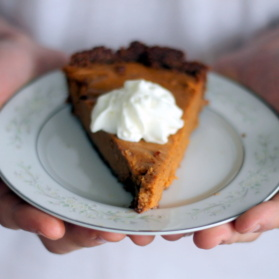 Lightened up sweet potato pie with whipped cream on a plate