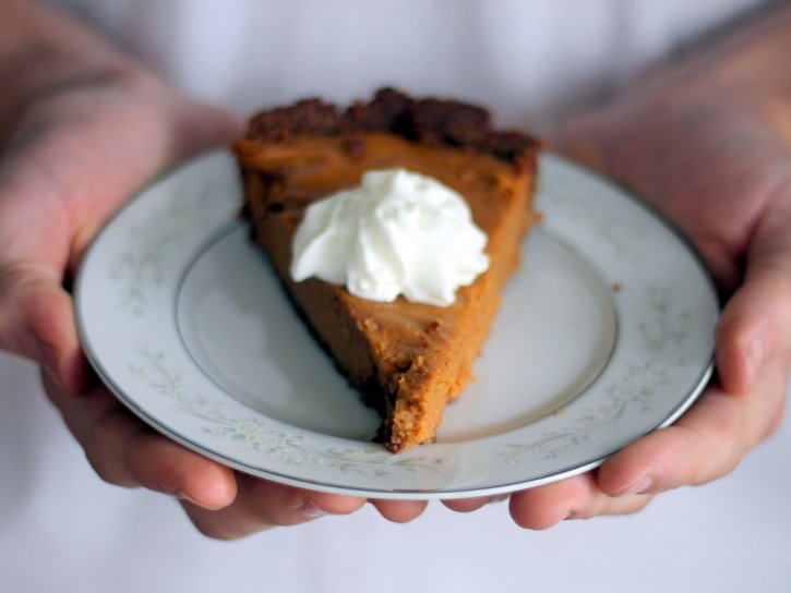 Lightened up sweet potato pie topped with whipped cream on a plate