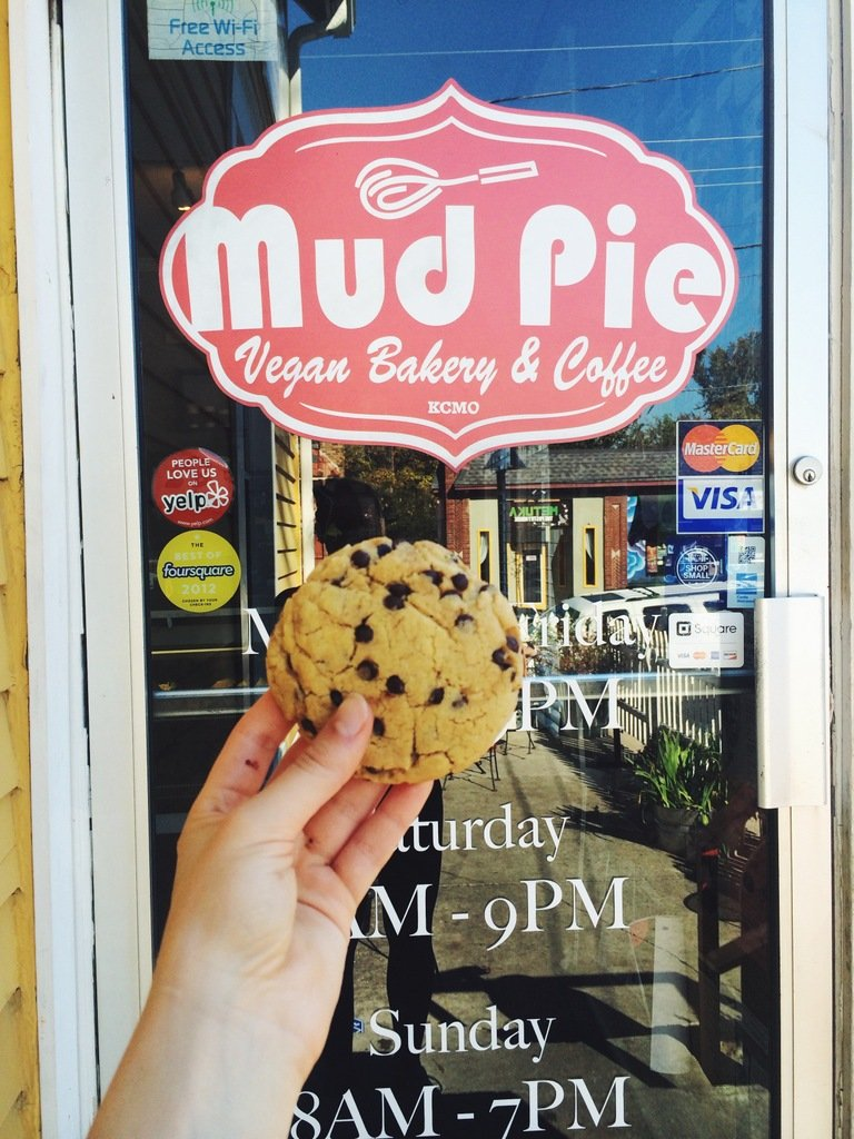 Holding a cookie in front of Mud Pie Vegan Bakery & Coffee