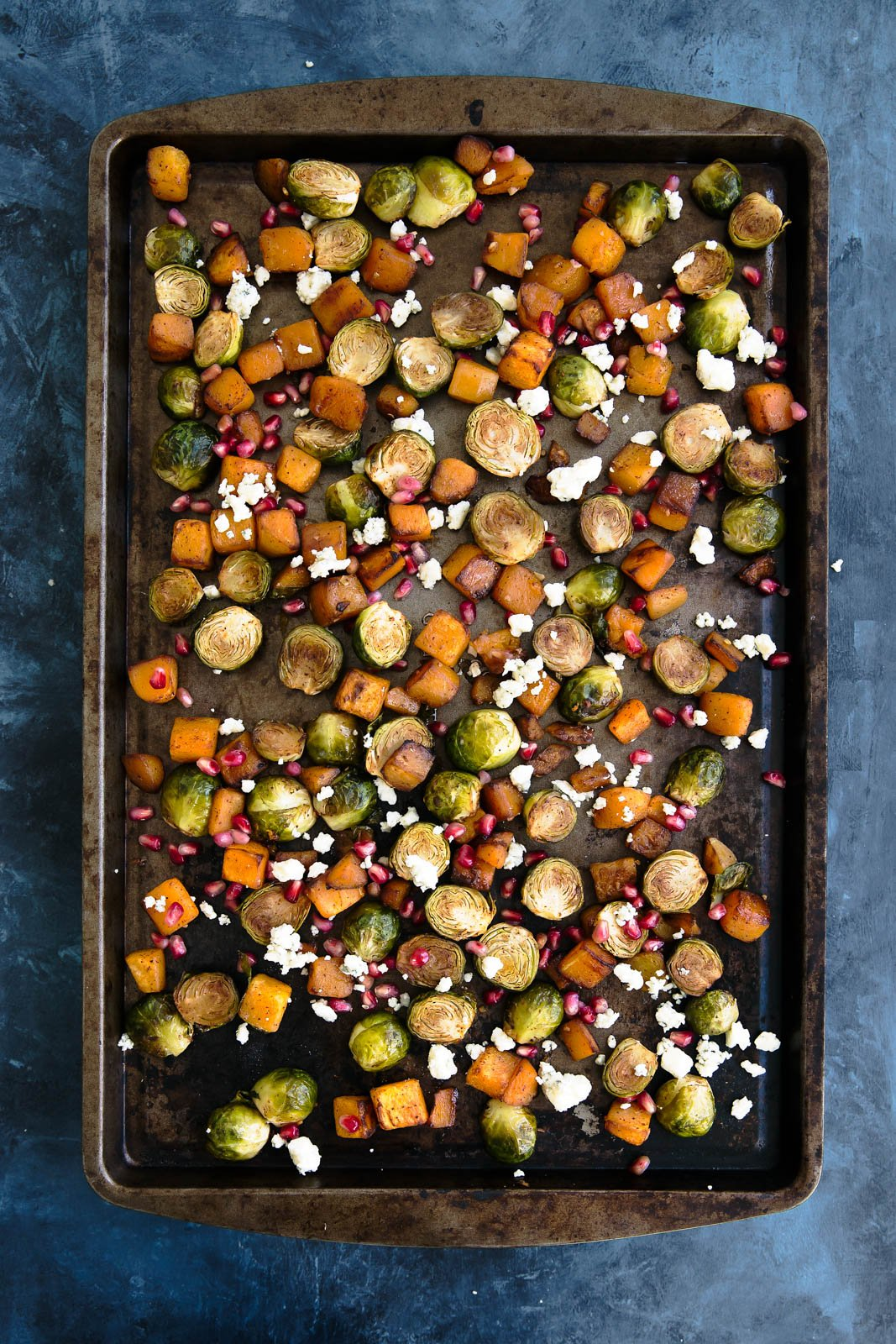 Roasted butternut squash and brussels sprouts with pomegranate and gorgonzola on a baking tray