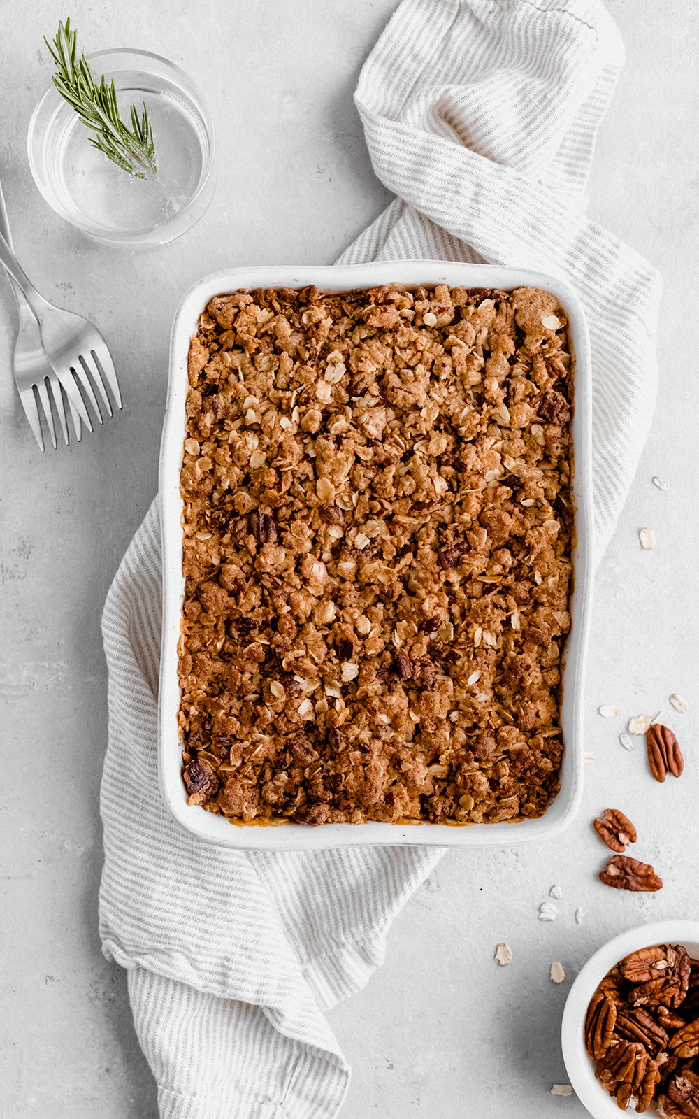 healthy sweet potato casserole in a baking dish on top of a white linen