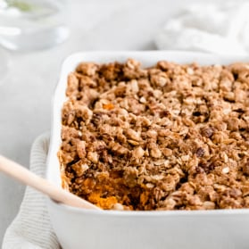 healthy sweet potato casserole in a baking dish with a wooden spoon