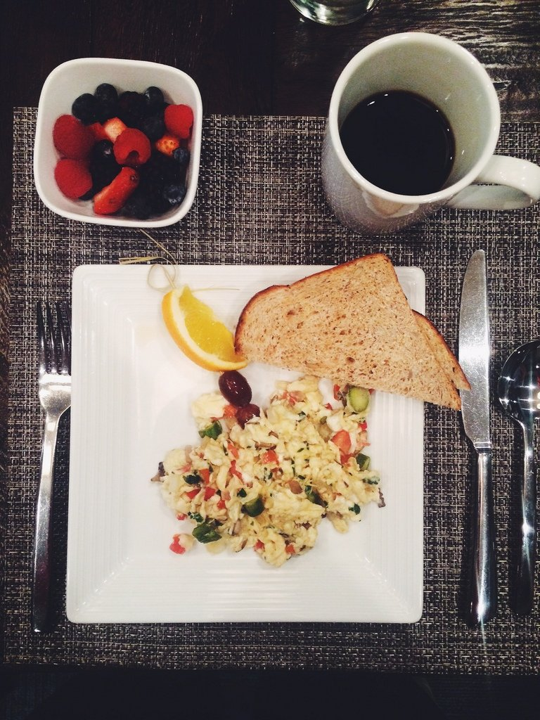 Plate with scrambled eggs, toast, a side of fruit and coffee