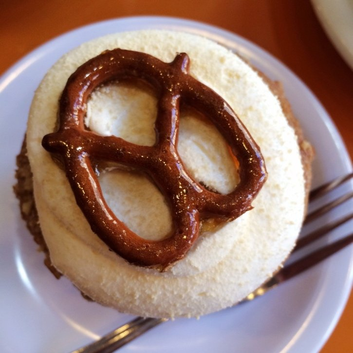 Top of a cupcake with frosting and a pretzel on top