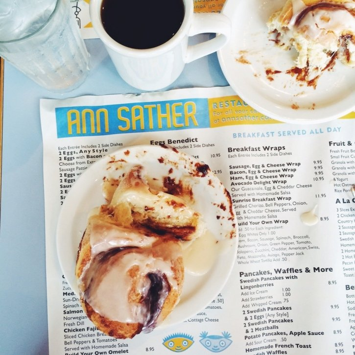 Cinnamon rolls on a plate on top of an Ann Sather menu