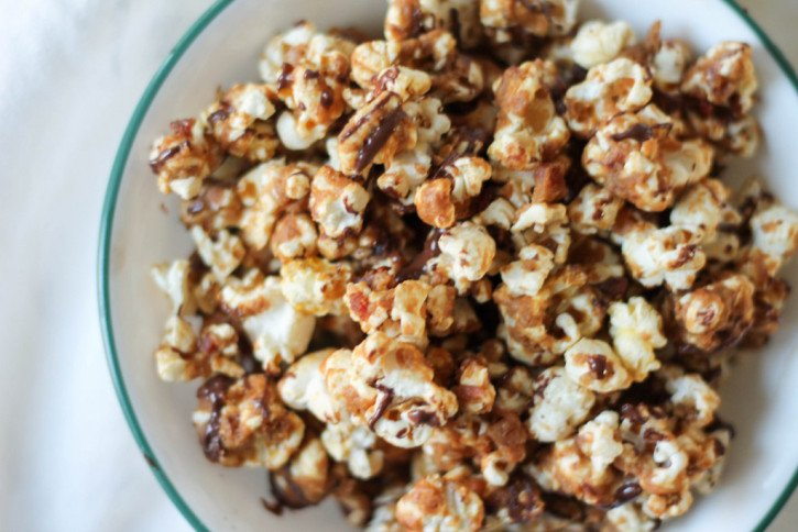 Bacon Peanut Butter Caramel Corn with a dark chocolate drizzle in a bowl