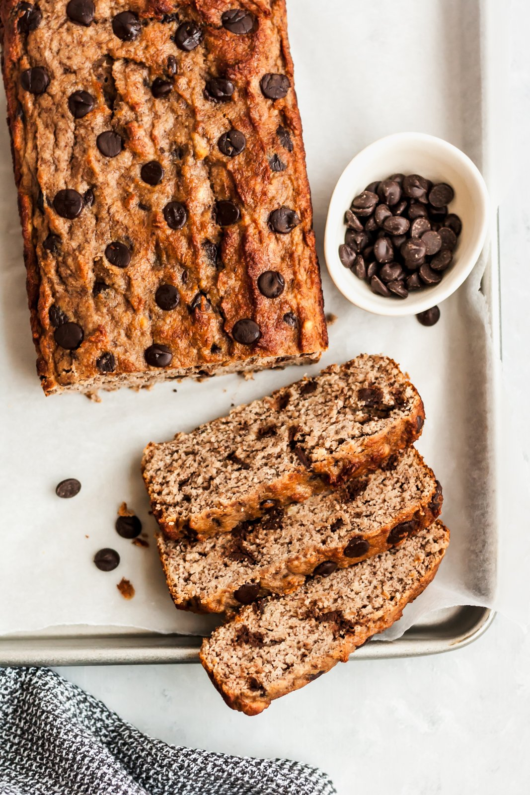 Paleo coconut flour banana bread on a baking sheet with a dish of chocolate chips
