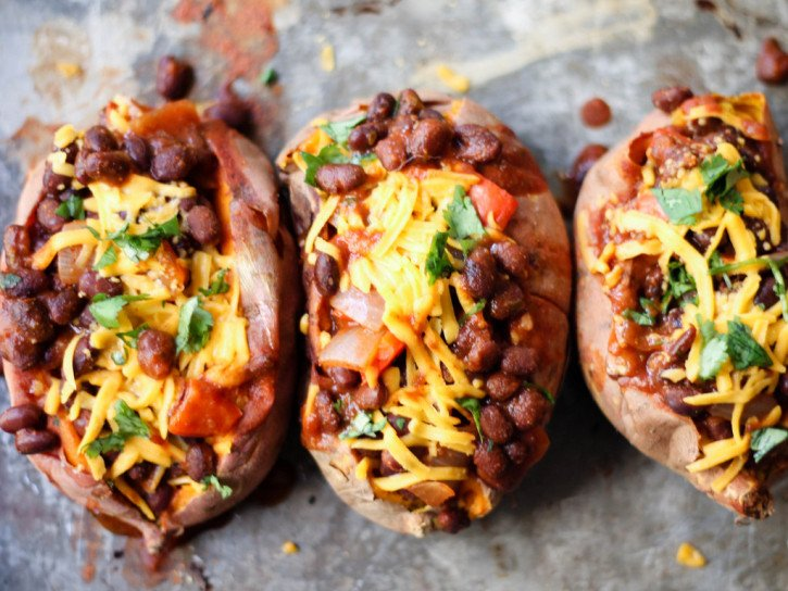 Chili stuffed sweet potatoes topped with cheese on a baking tray