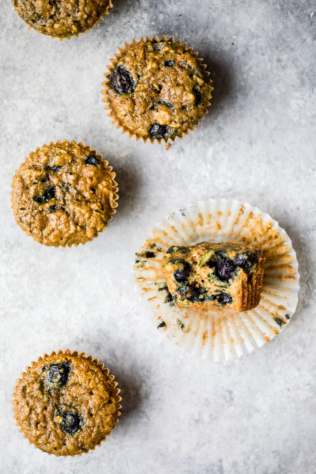 healthy blueberry zucchini muffins on a grey board