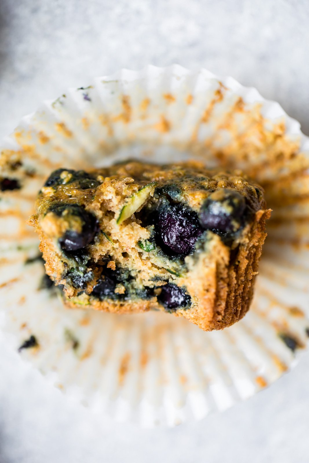 Healthy blueberry zucchini muffin with a bite taken out