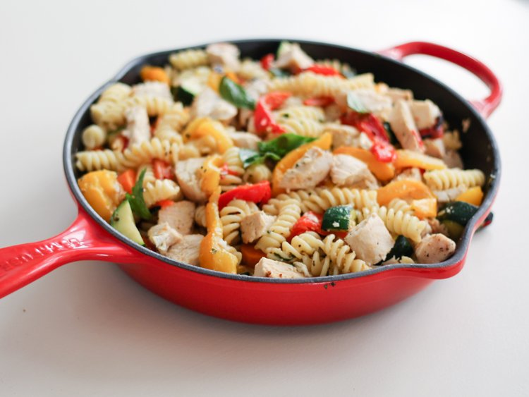 Garlic parmesan pasta with chicken and roasted bell peppers in a skillet
