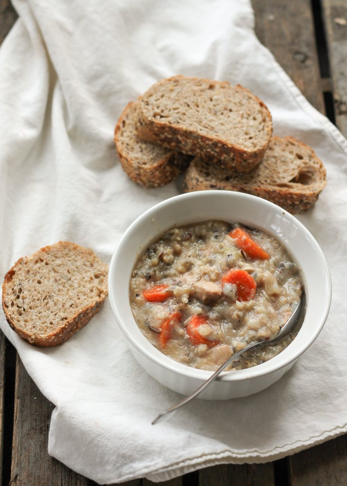 Chicken wild rice soup in a white bowl next to bread slices