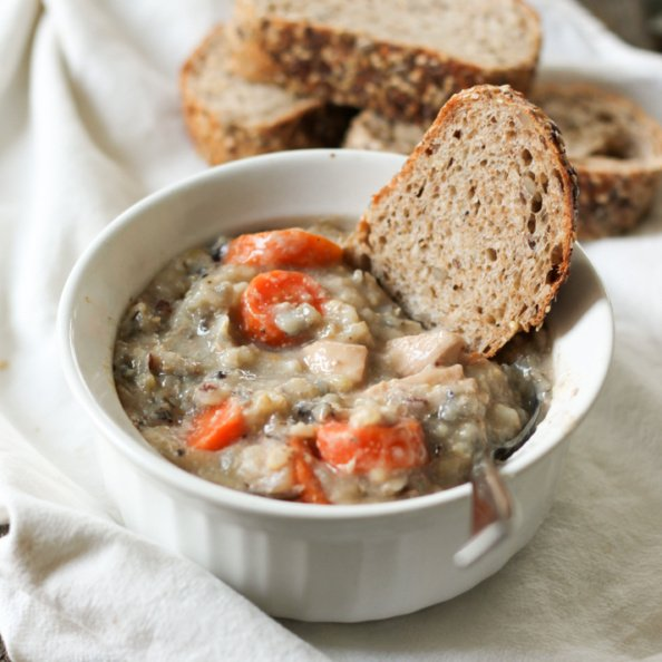 Chicken wild rice soup in a white bowl with bread