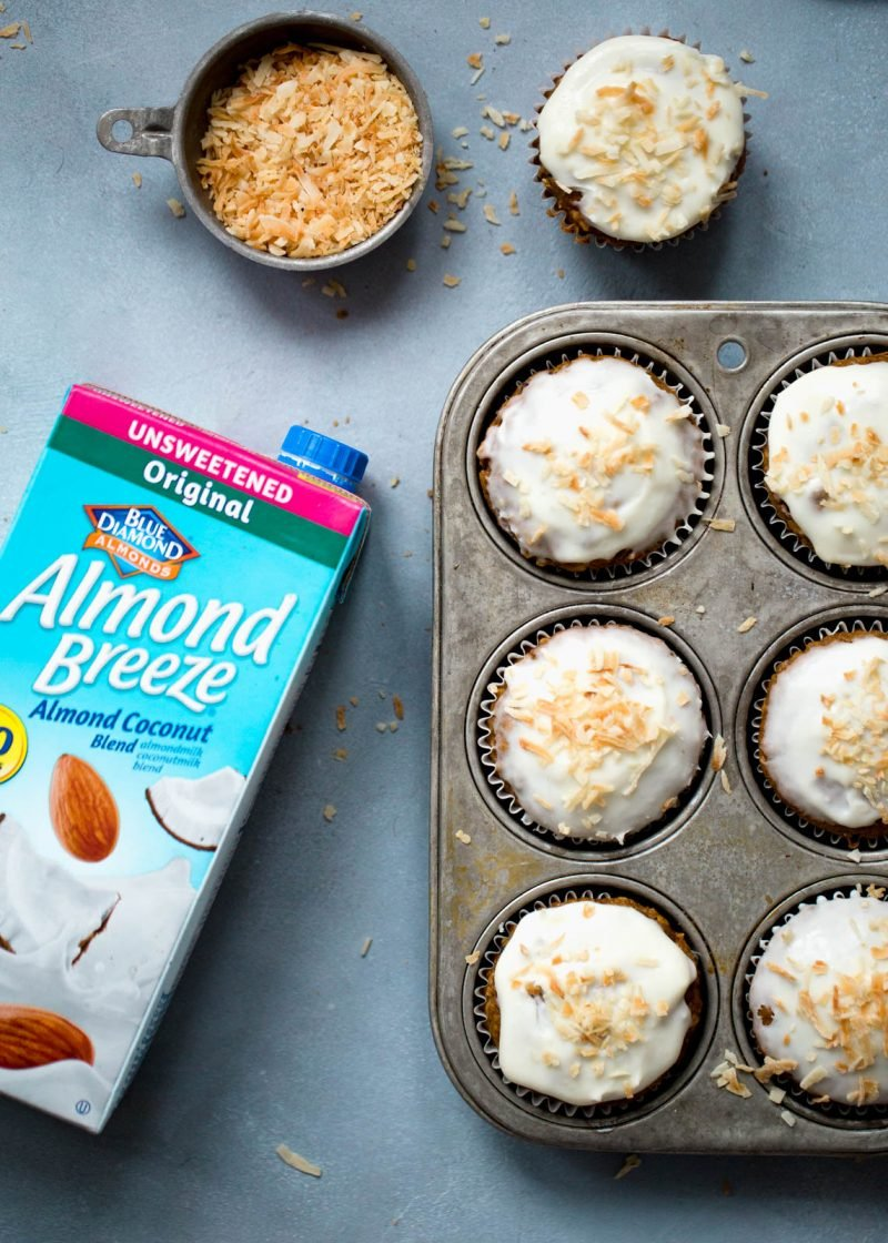 Healthy carrot cake muffins in a baking tray next to a carton of Almond Breeze almondmilk