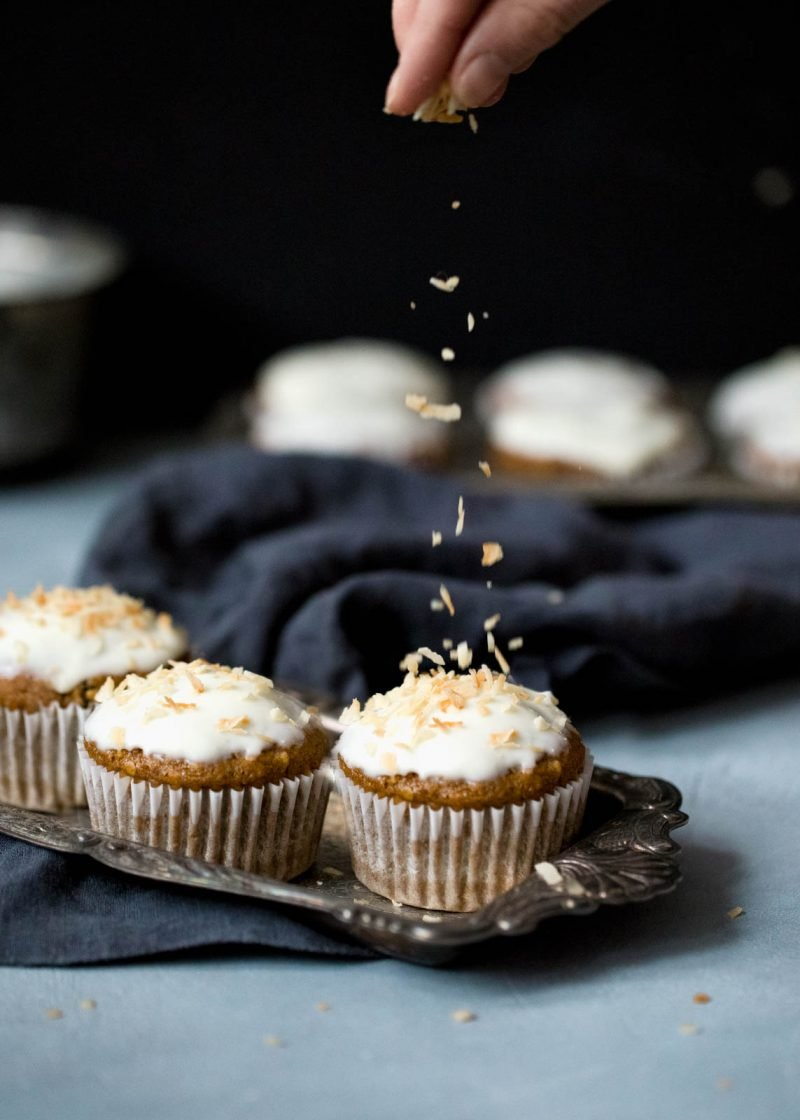 sprinkling coconut on a tray of healthy carrot cake muffins