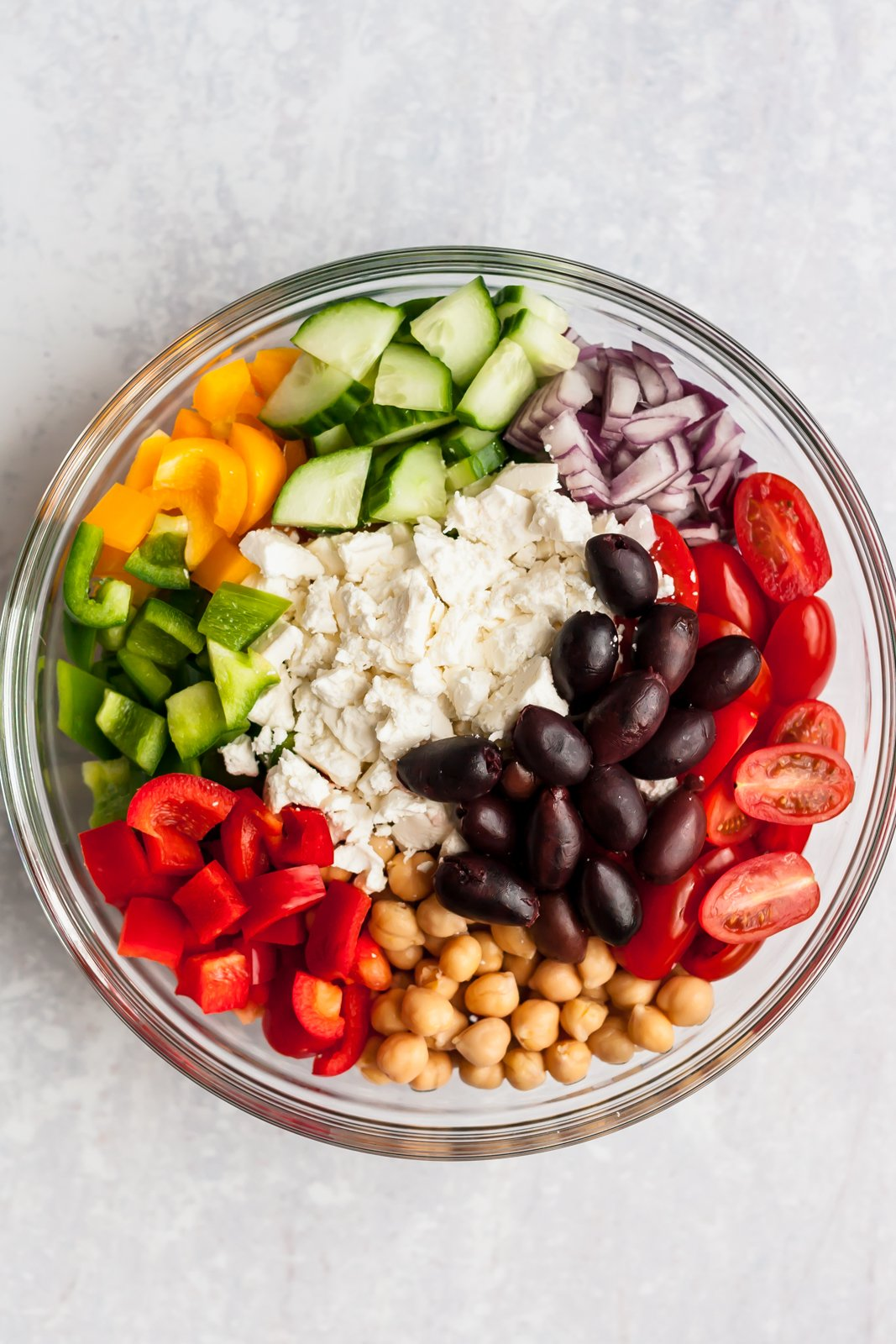 greek chickpea salad ingredients in a bowl on a board