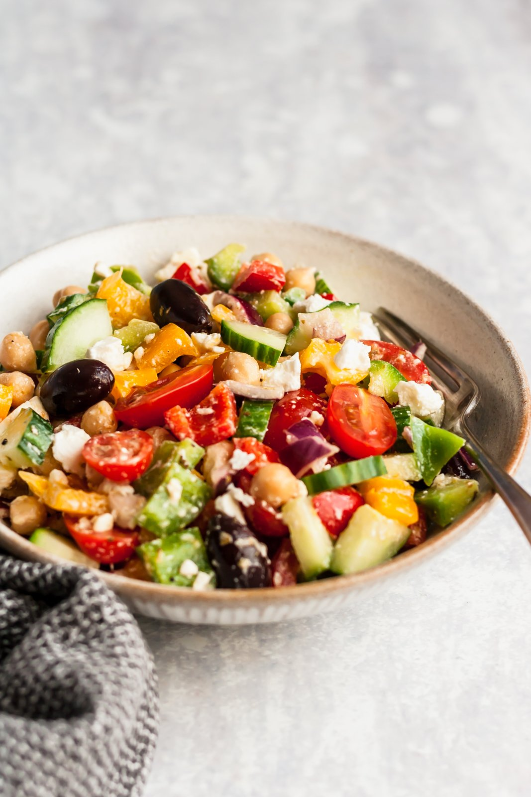 greek chopped chickpea salad in a bowl with a fork